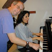 """Marty Buttwinick lends a """"helping hand"""" to pianist Gigi Boratgis during the rehearsal for Marty's jULIA eTUDES (no… we did not leave the Caps Lock key on–that's how Marty spells it!) compositions for music students."""