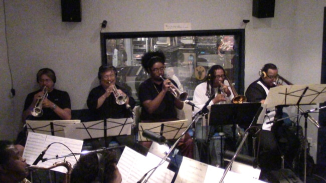 "Bill Churchville on 2nd Trumpet, Harry Kim on 1st Trumpet, Brandon Phillips on 3rd Trumpet, Duane Benjamin on Trombone and Robbie Hioki on Bass Trombone comprise the brass section for this ""Mel Carter Continues..."" session at Theta Sound Studio"